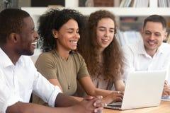 Glückliches multi ethnisches Forschungsteam, das unter Verwendung des Laptops zusammenarbeitet stockfotografie
