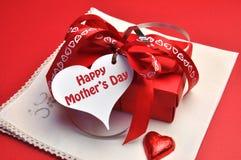 Glückliches Mutter-Tagesrot vorhanden mit Geschenkumbaumitteilung Stockfotos