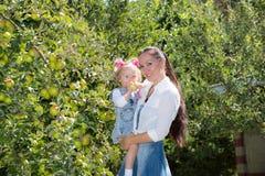 Glückliches Mutter- und Kindermädchen, das auf Natur umarmt Schöne Mutter und ihr Baby im Freien Stockbilder