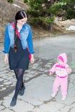 Glückliches Mutter- und Kindermädchen, das auf Straße lacht Das Konzept der netten Kindheit Stockbilder