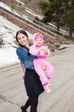 Glückliches Mutter- und Kindermädchen, das auf Straße umarmt und lacht Das Konzept der netten Kindheit Lizenzfreies Stockfoto