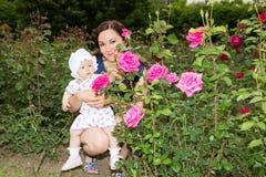 Glückliches Mutter- und Kindermädchen, das in den Blumen umarmt.  Schöne Mutter und ihr Baby draußen Stockfoto