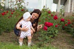 Glückliches Mutter- und Kindermädchen, das in den Blumen umarmt. Schöne Mutter und ihr Baby draußen Stockfotos