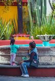 Glückliches Mutter- und Tochterspiel in der bunten Stadt, Guanajuato, Mexiko lizenzfreie stockbilder