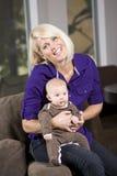 Glückliches Mutterholdingschätzchen auf Couch zu Hause Stockbild