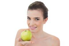 Glückliches natürliches braunes behaartes Modell, das einen grünen Apfel anbietet Lizenzfreies Stockfoto