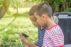 Glückliches nettes asiatisches Jungenspielspiel mit Smartphone sitzen auf Auto Stockbilder