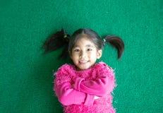 Glückliches nettes asiatisches Kinderlächeln auf grünem Gras mit rosa swetter Reihe stockfotografie