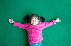 Glückliches nettes asiatisches Kinderlächeln auf grünem Gras mit rosa swetter Reihe stockfoto