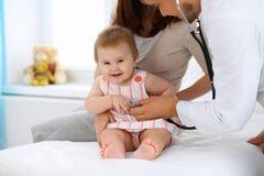 Glückliches nettes Baby mit ihrer Mutter an der Gesundheitsprüfung in Doktor ` s Büro Stockfotos