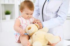 Glückliches nettes Baby nach Gesundheitsprüfung in Doktor ` s Büro Stockfotos