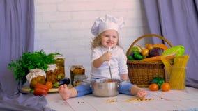 Glückliches nettes Kind in Chef ` s Hut im Küchenlachen, spielend stock footage