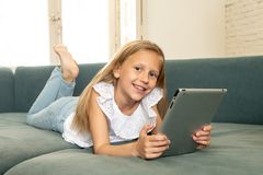 Glückliches nettes Kind, das im Internet mit Tablette mit großem Interesse lernt, spielt und surft Stockfoto