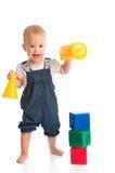 Glückliches nettes Kind, das mit den Blockwürfeln lokalisiert auf Weiß spielt Lizenzfreies Stockfoto