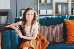 Glückliches nettes Kindermädchen, das auf gemütlicher Couch im modernen Wohnzimmer sitzt Stockbild