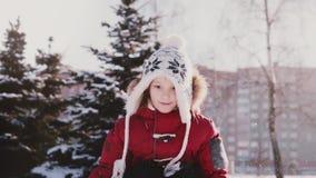 Glückliches nettes kleines europäisches Mädchen im Winter kleidet werfenden Schnee in der Luft und betrachtet Kamera und lächelnd stock video