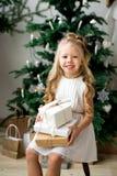 Glückliches nettes kleines lächelndes Mädchen mit Weihnachtsgeschenkbox Frohe Weihnachten und frohe Feiertage stockfoto