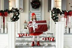 Glückliches nettes kleines lächelndes Mädchen mit Weihnachtsgeschenkbox Frohe Weihnachten und frohe Feiertage stockfotos