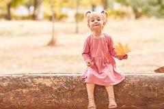 Glückliches nettes kleines Mädchen, das auf einem Parkhintergrund spielt Herbstspaßkonzept Kopieren Sie Platz lizenzfreie stockbilder