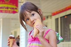 Glückliches nettes kleines Mädchen, das draußen Eiscreme isst Stockfotos