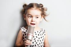 Glückliches nettes kleines Mädchen, das ein Lied auf Mikrofon singt Grauer Hintergrund Stockfotos