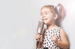 Glückliches nettes kleines Mädchen, das ein Lied auf Mikrofon singt Grauer Hintergrund Lizenzfreies Stockfoto