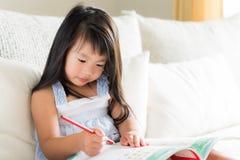 Glückliches nettes kleines Mädchen, das roten Bleistift lächelt und hält stockbild