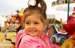 Glückliches nettes lächelndes Reiten des kleinen Mädchens auf Karussell am Sommertag Lizenzfreies Stockfoto
