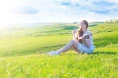 Glückliches nettes Mädchen auf dem grünen Gebiet mit Gitarre bei Sonnenuntergang Stockfotografie
