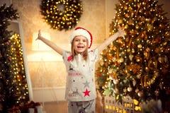 Glückliches nettes Mädchen in den Weihnachtspyjamas, Sankt-Helferhut hob ihre Hände oben an stockbilder