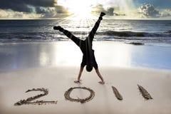 Glückliches neues Jahr 2011 auf Strand des Sonnenaufgangs Stockfotos