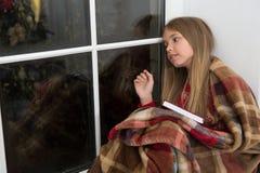 Glückliches neues Jahr Der kleine Leser, der im Plaid eingewickelt wird, sitzen auf Fensterbrett Das Bilderbuch der Kinder Magisc stockbilder