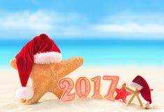 Glückliches neues Jahr Starfish in Sankt-Hut auf Sommerstrand Lizenzfreies Stockfoto