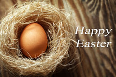 Glückliches Osterei im Nest auf hölzernem Hintergrund Stockfoto