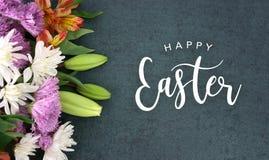 Glückliches Ostern-Kalligraphie-Feiertags-Skript mit bunten Frühlings-Blumen über Tafel-Hintergrund-Beschaffenheit Stockfotografie