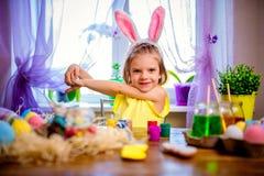 Glückliches Ostern-Mädchen in den Häschenohren, die zu Hause Eier, kleines Kind malen Frühlingsfeiertag stockfotos