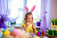 Glückliches Ostern-Mädchen in den Häschenohren, die zu Hause Eier, kleines Kind malen Frühlingsfeiertag lizenzfreies stockbild