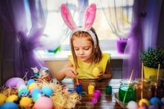 Glückliches Ostern-Mädchen in den Häschenohren, die zu Hause Eier, kleines Kind malen Frühlingsfeiertag stockfotografie