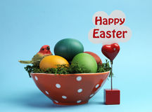 Glückliches Ostern-Stillleben mit Regenbogenfarbe eggs gegen einen blauen Hintergrund mit Zeichen Stockfotografie