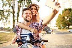 Glückliches Paar auf dem Roller, der selfie Foto auf Smartphone macht Stockfotografie