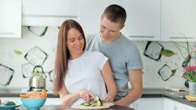 Glückliches Paar auf der hellen Küche zusammen kochend Shreding Gemüse der jungen Frau, zum des gesunden Mittagessens vorzubereit stock video footage