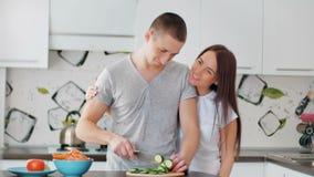 Glückliches Paar auf der hellen Küche zusammen kochend Shreding Gemüse der jungen Frau, zum des gesunden Mittagessens vorzubereit stock footage