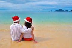Glückliches Paar in chtistmas Hüten auf tropischem Strand Stockbilder