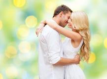 Glückliches Paar, das über Hintergrund der grünen Lichter umarmt Lizenzfreies Stockbild