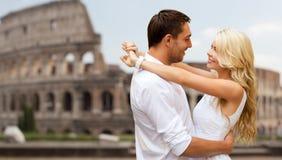 Glückliches Paar, das über Kolosseum umarmt Stockbild