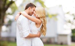 Glückliches Paar, das über Sommerhaushintergrund umarmt Lizenzfreie Stockbilder