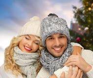 Glückliches Paar, das über Weihnachtsbaum umarmt stockfotos