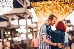 Glückliches Paar, das am Abend auf helle Girlanden umfasst stockfotos