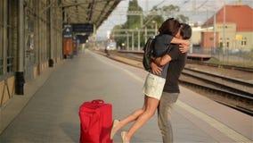 Glückliches Paar, das auf Bahnhofsplattform umfasst Abschied an der Bahnstation, am jungen Mädchen und am Kerl, die an küssen stock footage