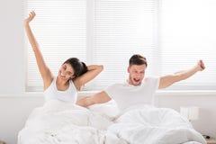 Glückliches Paar, das auf Bett aufwacht lizenzfreie stockfotografie